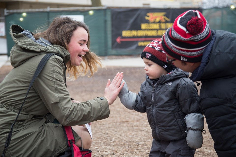 A preschooler from the University of Guelph Child Care and Learning Centre gets a high-five after handing a 'good luck' card to a university student prior to the start of exams. Kenneth Armstrong/GuelphToday