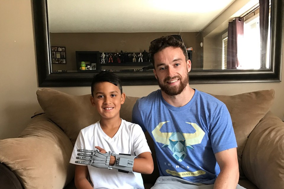 Jerry Ennett poses for a photo with Jordan, a boy who uses a prosthetic hand designed by Ennett. The prosthetic can be built for about $25 worth of materials. Photo provided