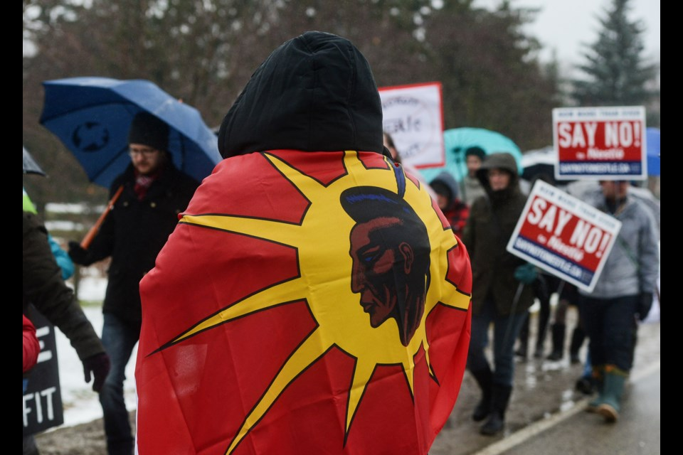 Indigenous activist Eryn Wise, with a First Nations flag around her shoulders, watches the procession of protesters make its way to the Nestle plant in Aberfoyle on Saturday. Tony Saxon/GuelphToday