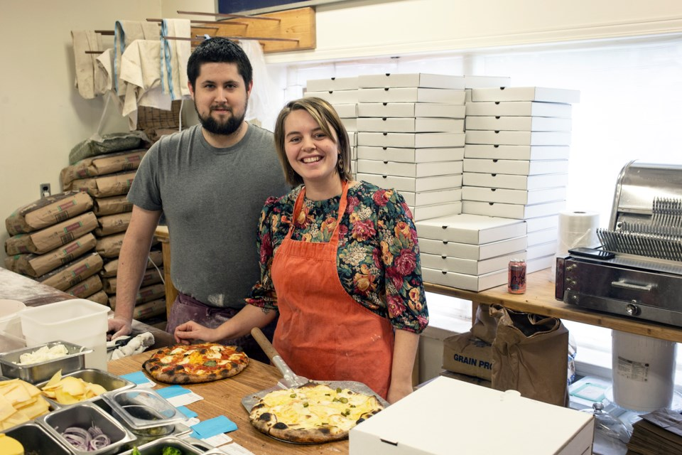 Jesse Wallace and Abby Richter are two of four people operating the pop-up Pie by Night pizza shop on Sundays at Polestar Hearth bakery. Kenneth Armstrong/GuelphToday