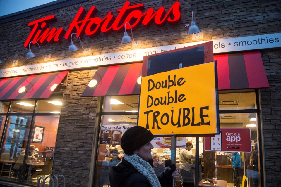 Donna Jennison walks in front of the Tim Hortons on Victoria Rd. S. during an action in solidarity with workers of the chain, many of whom have received a cut to benefits and breaks in light of an increase in minimum wage. Kenneth Armstrong/GuelphToday