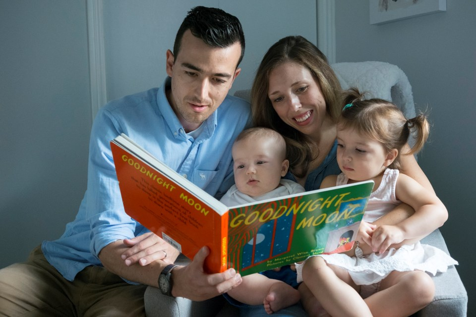 Kevin Page and Meaghan Forestell-Page read Goodnight Moon with their daughter Mae and two-month-old Sam. Every newborn in Guelph receives the book as part of the Born to Read program. Kenneth Armstrong/GuelphToday