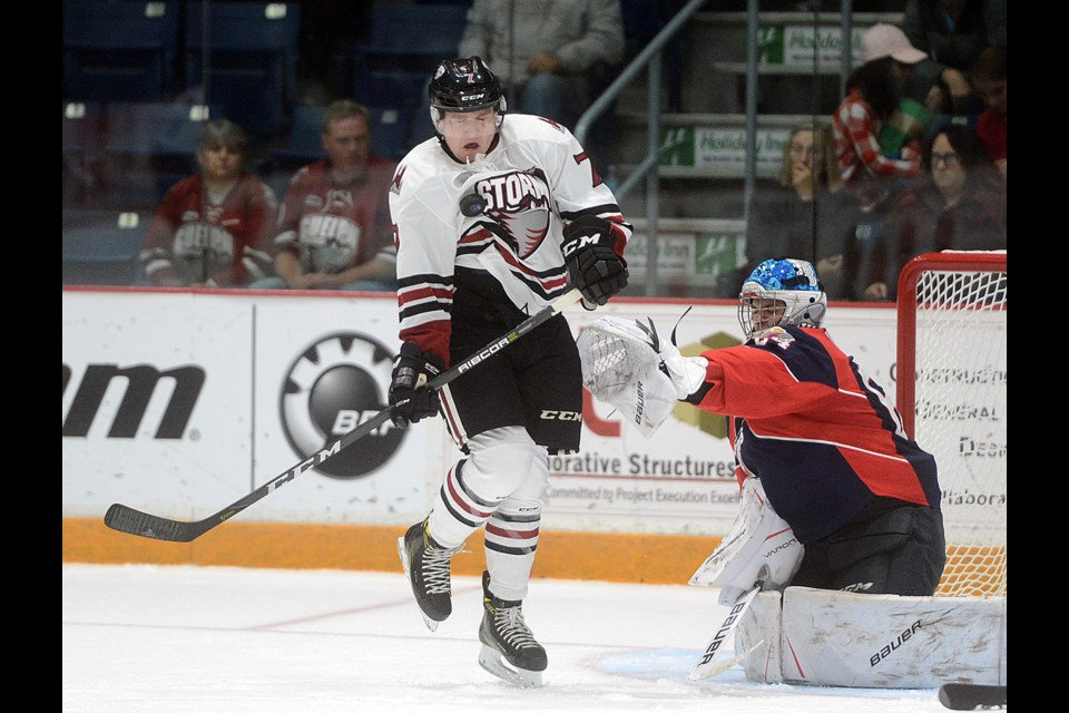The Guelph Storm's Zach Poirier gets hit by a point shot as he tries to screen Windsor Spitfires goaltender Michael DiPietro Friday, Oct. 6, 2017, at the Sleeman Centre. Tony Saxon/GuelphToday