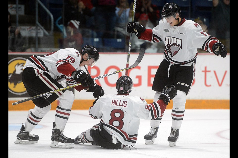 Guelph Storm teammates Isaac Ratcliffe, left, and Alexey Toropchenko, right, help Cam Hillis celebrate his first OHL goal Saturday, Oct. 7, 2017, at the Sleeman Centre. Tony Saxon/GuelphToday