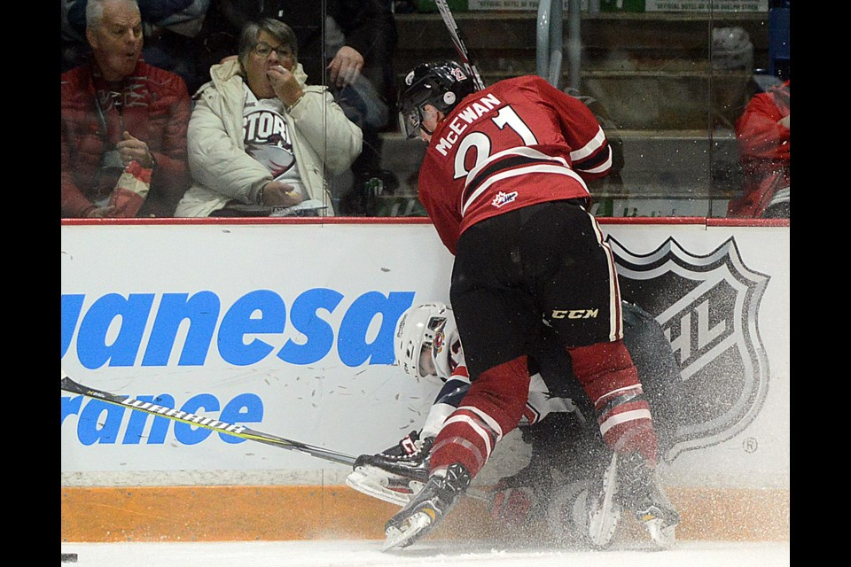 The Windsor Spitfires' Louka Henault is driven in to the boards by the Guelph Storm's James McEwan Friday, Jan. 19, 2018, at the Sleeman Centre. Tony Saxon/GuelphToday