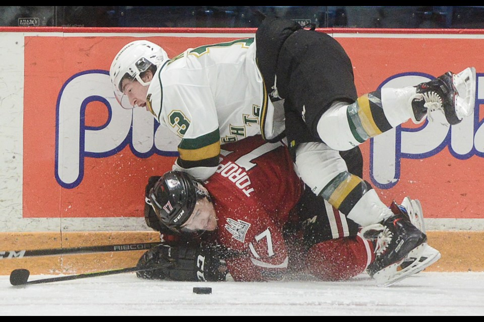 Tyler Rollo of the London Knights buries the Guelph Storm's Alexey Toropchenko with a check Sunday at the Sleeman Centre. Tony Saxon/GuelphToday