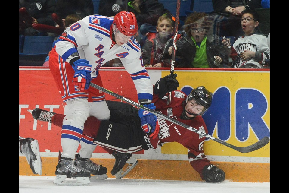 Logan Stanley of the Kitchener Rangers bowls over the Guelph Storm's Ryan Merkley Sunday at the Sleeman Centre. Tony Saxon/GuelphToday