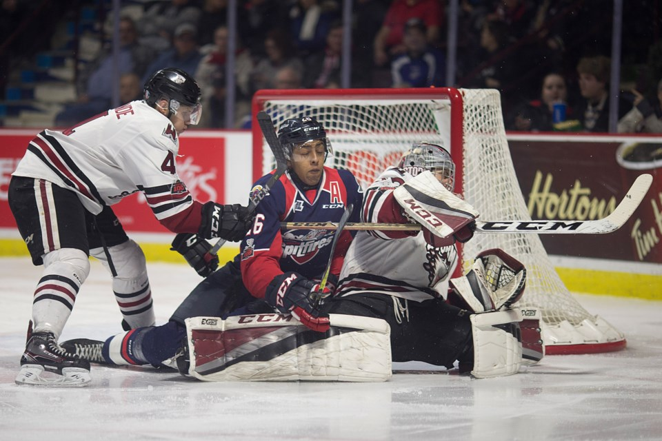 Cole Purboo of the Windsor Spitfires gets tied up with Guelph Storm goaltender Anthony Popovich and defenceman Owen Lalonde Thursday in Windsor. Dax Melmer/Windsor Star