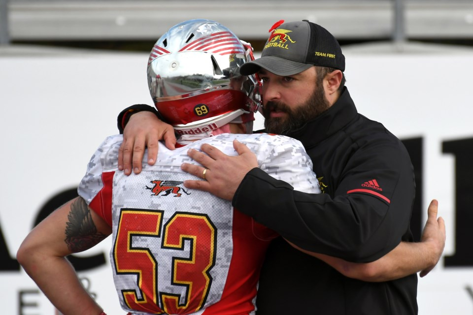 Head coach Kevin MacNeill of the Guelph Gryphons and linebacker Luke Korol embrace following Guelph's semifinal loss to the Western Mustangs Saturday at London. Rob Massey for GuelphToday