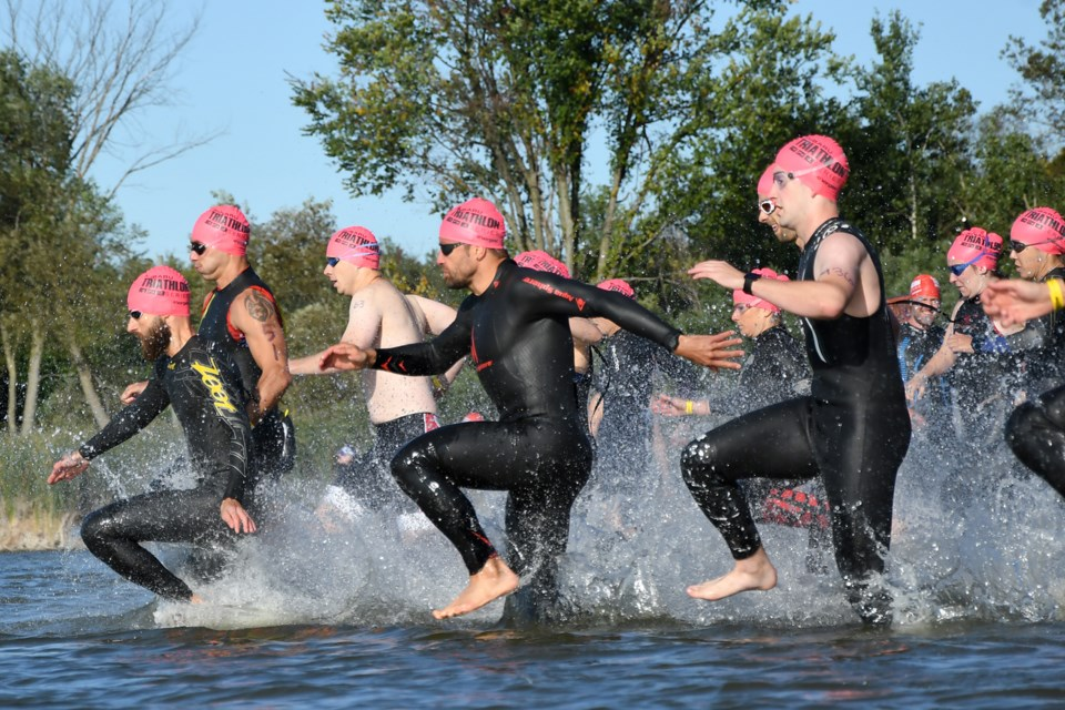 Competitors in the second wave dash into Guelph Lake to start the swim leg of Saturday's Guelph Two sprint triathlon at the Guelph Lake Conservation Area. Rob Massey for GuelphToday