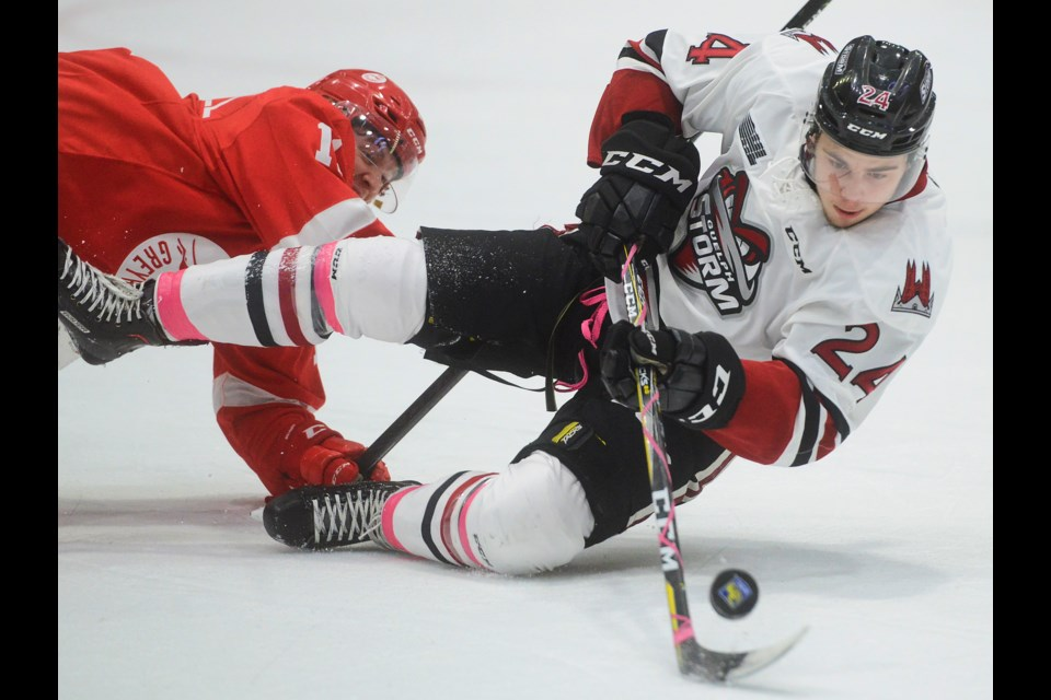 The Guelph Storm's Tag Bertuzzri gets knocked down by a SaultStoe. Marie Greyhounds player. Tony Saxon/GuelphToday