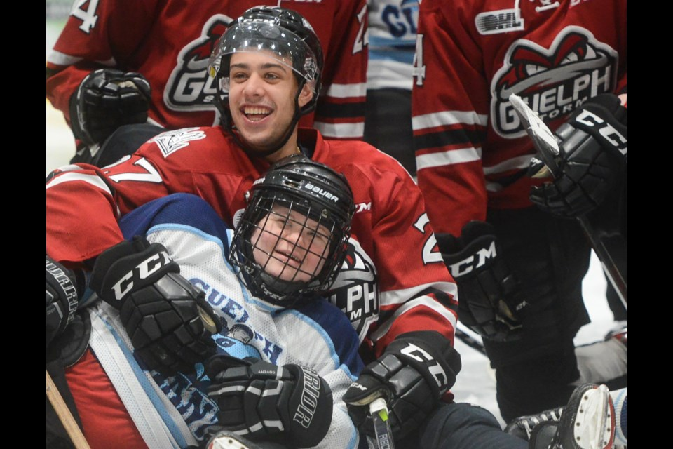 The Guelph Storm's Dom Commisso is all smiles while posing for post-game pics with members of the Guelph Giants hockey team Saturday at the Sleeman Centre. Tony Saxon/GuelphToday