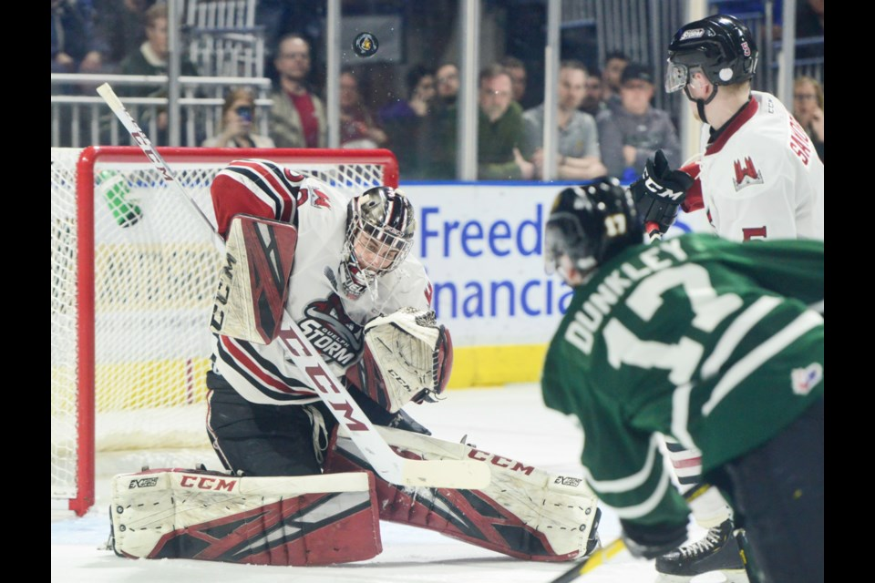 Guelph Storm goaltender Anthony Popovich makes a save on a high shot by London's Nathan Dunkley Sunday in London. Tony Saxon/GuelphToday