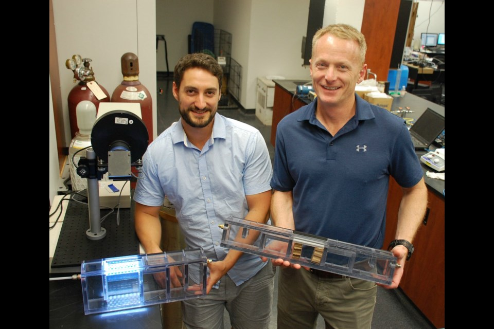 David Wood (left) and Bill Van Heyst are pictured in their University of Guelph lab with two SmogStop prototypes. Photo by Alaina Osborne/SPARK.