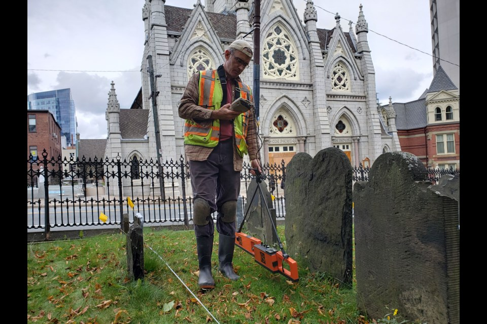 Dr. Jonathan Fowler operating the EM38 conductivity and susceptibility measuring instrument during an archaeological geophysical survey of the Old Burying Ground. (Photo credit : Max Tardy)