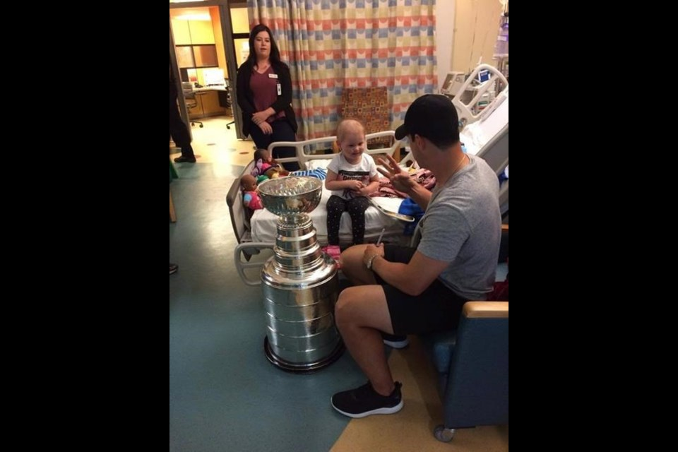 Sidney Crosby visits with three-year-old Harper Saunders, who is being treated for leukemia, at the IWK Health Centre in Halifax on Sunday in this handout image. Crosby spent about an hour and a half roaming from room to room, visiting with kids and families and taking photos with 'Stanley.' (THE CANADIAN PRESS/HO)