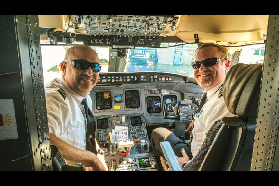 Captain Jeff Villarreal, left, and First Officer Nathan Zoeller share a peek inside the cockpit of the Bombardier CRJ-700. (Cathy Donaldson)
