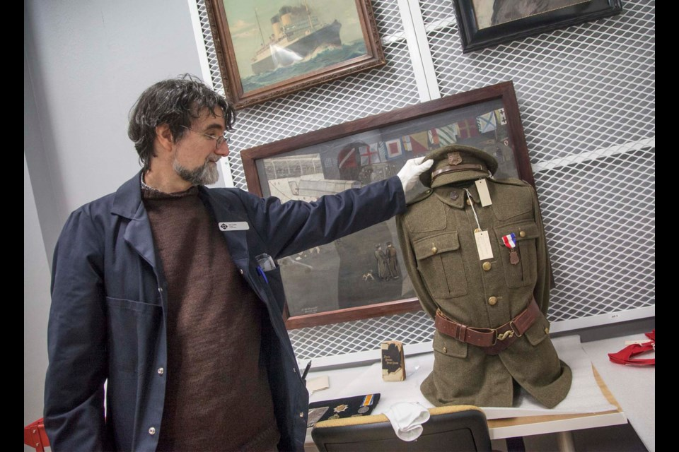 Dan Conlin, curator at the Canadian Museum of Immigration at Pier 21, displays a First World War uniform worn by Sapper Joseph Parris, of No. 2 Construction Battalion.