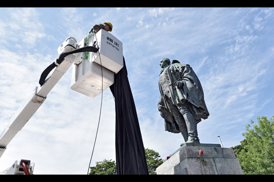 A city worker prepares to cover a statue of Edward Cornwallis on Saturday in Halifax.  (CHRISTIAN LAFORCE / Local Xpress)
