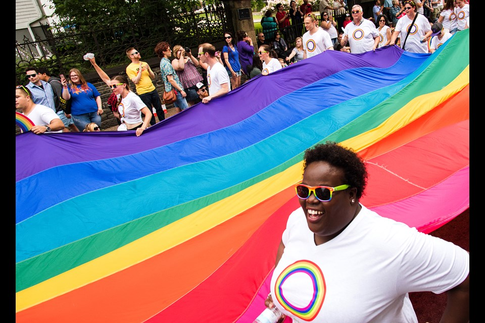 Participants carry a giant rainbow flag on Barrington Street during the 2016 Halifax Pride parade Saturday.