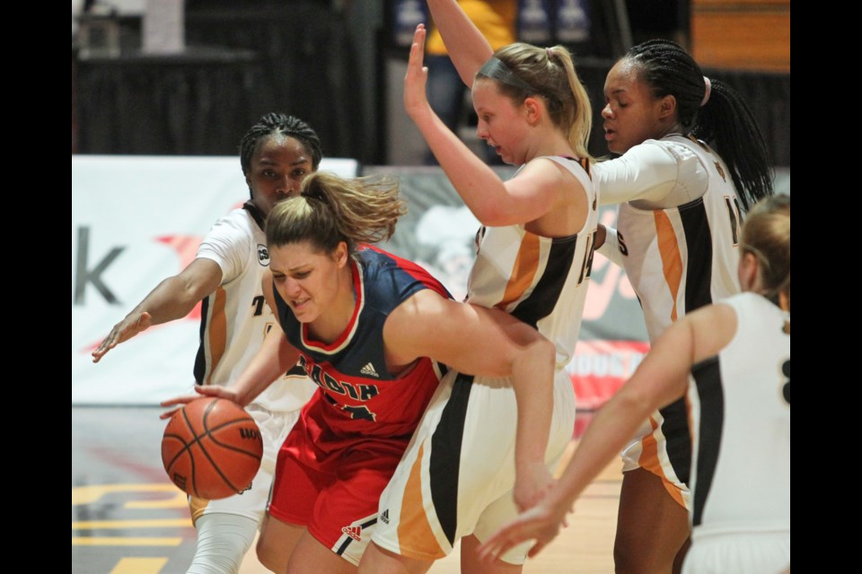 Acadia Axewomen's Alexandra Berry drives to the hoop against Dalhousie Tigers' Michele Tchiakova, Claire Hickman and Robertha Charles during AUS basketball action at Dalplex on Tuesday. (TIM KROCHAK / Local Xpress)
