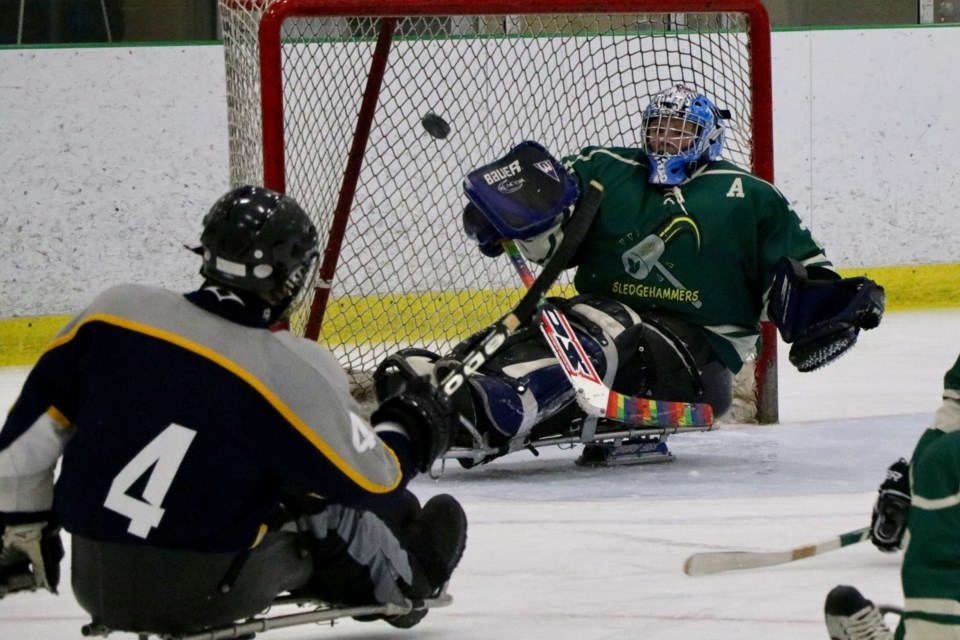 The P.E.I. Icebreakers' Jason Webster lifts the puck over Cape Breton Sledge Hammers goalie Jennifer Pearcy to score late in the third period of the East Coast Sledge Hockey Challenge gold medal game Sunday. (ERIC WYNNE / LocalXPress)