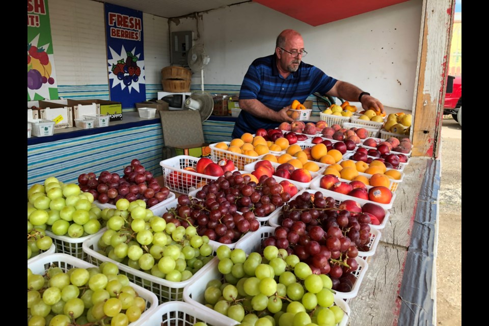 Todd Bell, owner of B&B Fruit Stand, arranges his produce in between customers. Photo by Jason G. Antonio