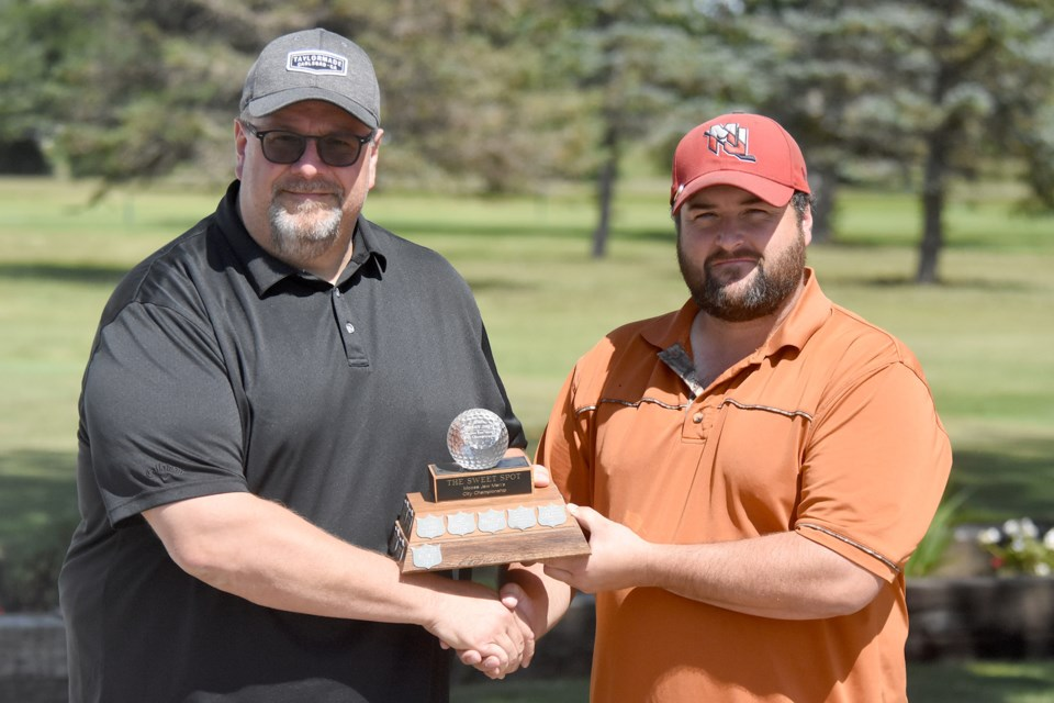 Moose Jaw city men's golf champion Nick Lepine accepts the championship trophy from The Sweet Spot general manager Carlo Berardi.