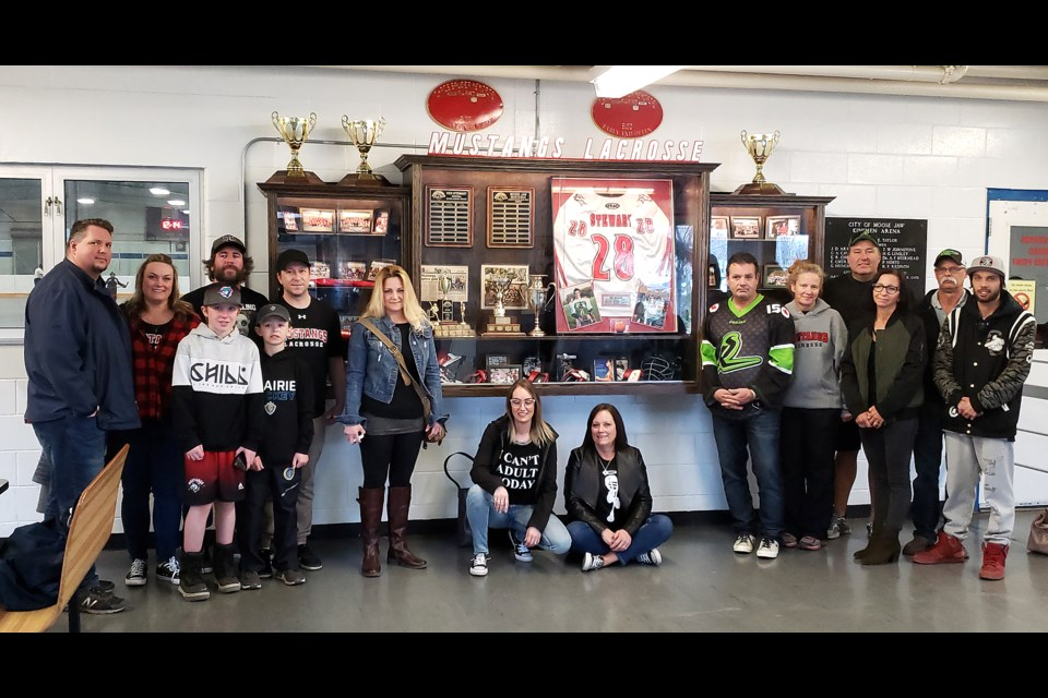 Members of the Moose Jaw Lacrosse Association community gather for a photo around the new display in the Kinsmen Arena.