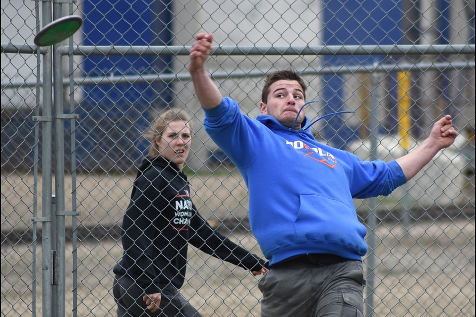 Weyburn's Alex Lund unloads a throw in the junior boys discus as a fellow competitor looks on. Lund would win the event with a 34.74 metre effort.