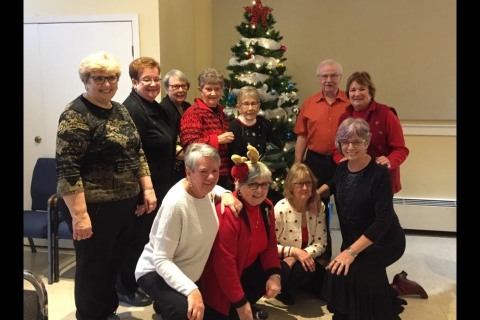 Kitchen staff and lunch organizers gathered around the Christmas tree at the Aurora Bridge Club's annual holiday lunch and bridge event Dec. 2.