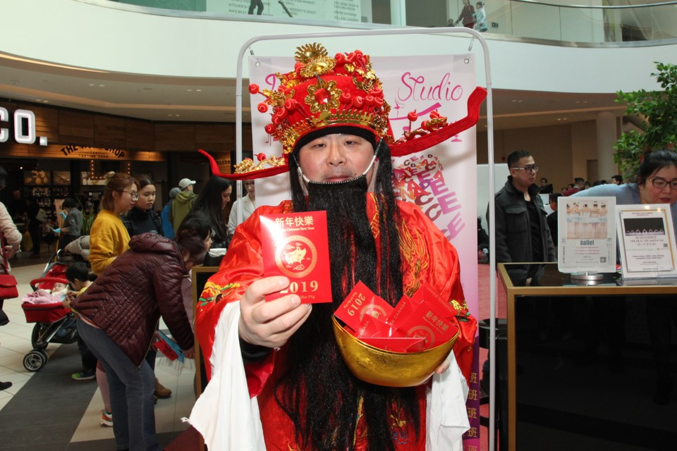 The God of Fortune hands out the traditional red envelopes of lucky money at the Northern Toronto Lunar New Year Celebration at Upper Canada Mall yesterday.  Greg King for NewmarketToday