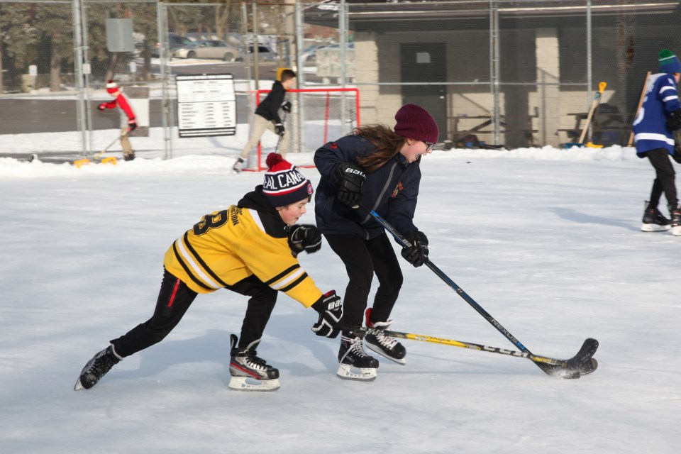 Luke and Avery McElroy battle over the puck  at the Lions Park Community Ice Rink.  Greg King for NewmarketToday