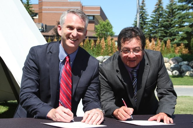 Bill Best, left, president of Cambrian College, and  Ron Sarazin, chair of the Circle for Indigenous Education at Cambrian College, sign the Indigenous Education Protocol during a ceremony at the Sacred Arbour on the main campus on June 20.