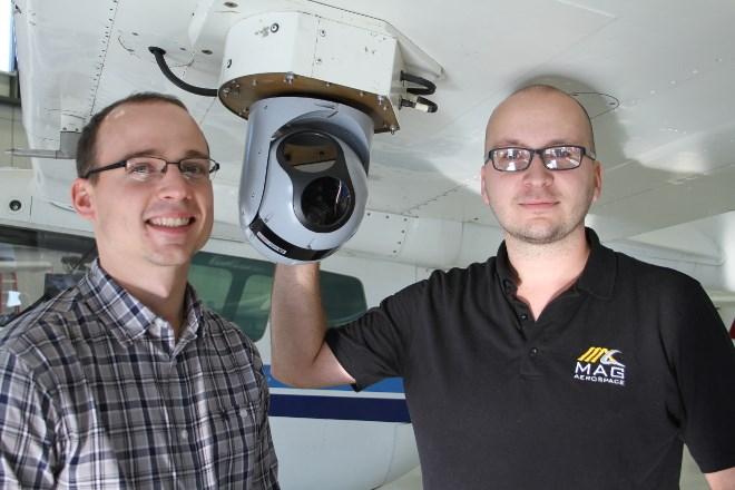 From left, Jason Fogg, VP of operations and Mike Ciezadlo, program manager, imagery, and both of Mag Aerospace, pose with a electronic optics and infrared sensor that is part of the sensor system Discovery Air Fire Services uses to spot and analyze blue-green algae blooms in waterways. Discovery Air is joining MAG Aerospace to offer more services.