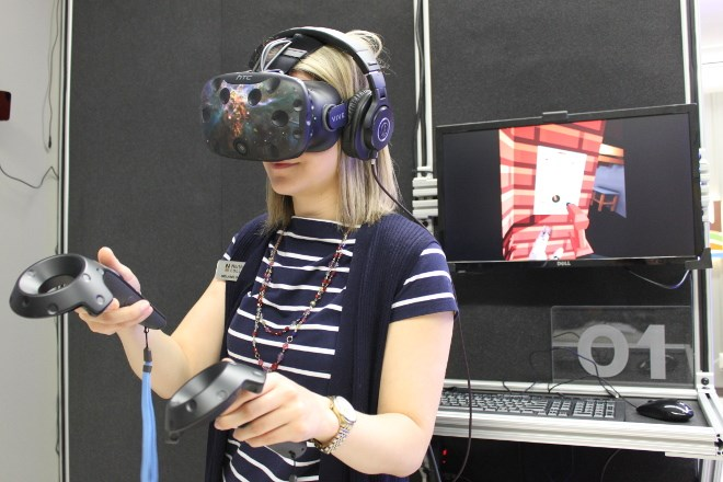 Wearing a virtual reality headset and holding handsets that allow her to manipulate onscreen equipment, communications officer Mélanie Watson demonstrates how the new VR programming works at Northern College.