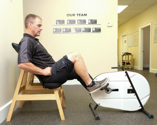 André Riopel demonstrates how to use the Viscus, a therapeutic pedalling machine he invented to help speed healing and improve mobility in patients. (Photo supplied)