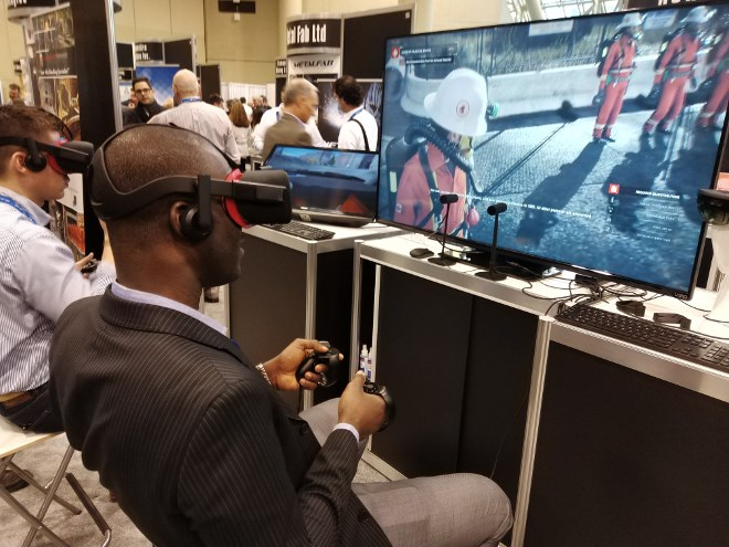 Visitors partake in virtual reality mine rescue demonstration simulations at NORCAT's booth at PDAC in early March. The innovation mill debuted the experimental program, along with a simulation of a Load, Haul, Dump driving simulation and an augmented reality training module for a fire extinguisher.