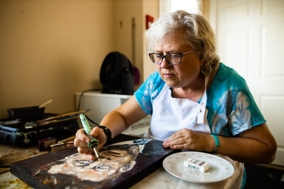Penny Gunderson works on encaustic artwork in her home on Aug. 29. Gunderson, who suffers from autoimmune diseases and mental health issues, was selected to be a part of that SPARK Disability Art Festival in Calgary.