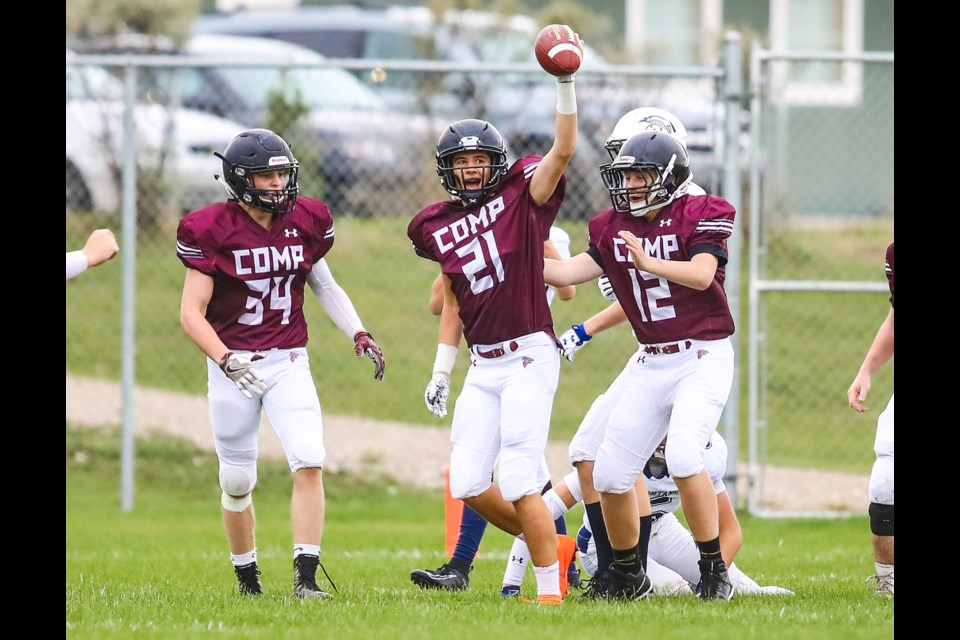 Foothills Falcons defensive back Jamison Strilchuk (21) holds up the ball after a key interception against the Strathmore Spartans on Sept. 6. He's flanked by Falcons teammates Sam Simard (34) and Abraham Wallace (12). Foothills won the game by a 22-8 score. (BRENT CALVER/Western Wheel)
