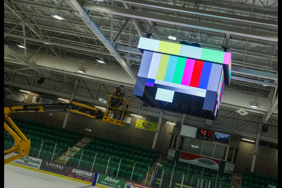 Pason Centennial Arena's new centre ice screen gets hoisted into place on Sept. 5. (BRENT CALVER/Western Wheel)