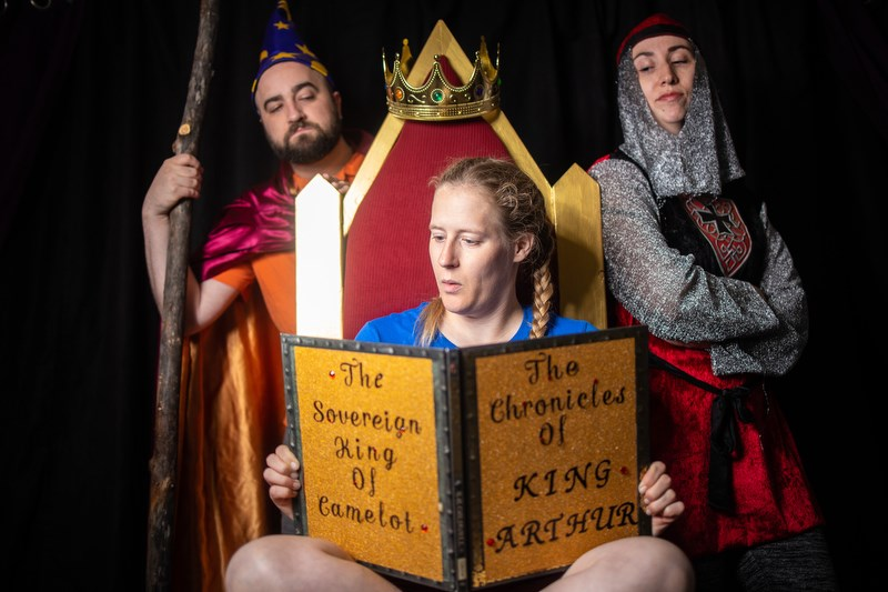 Kelly Malcolm, playing Win, is transported to a different world while reading the fantasy of King Arthur in a rehearsal for Goodger Pink Family Theatre's production of King Arthur.  (Photo by Brent Calver/Western Wheel)