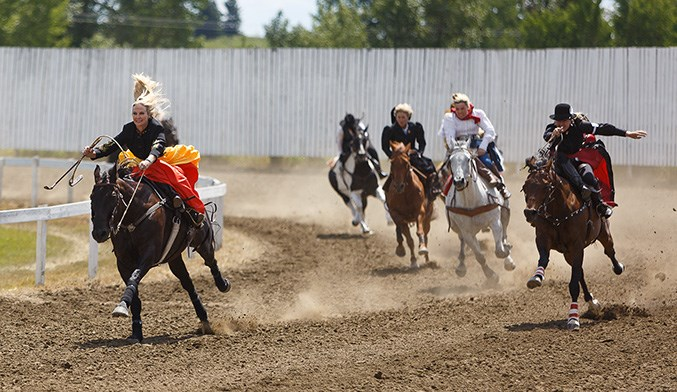 Erin Thompson, left, competes in the Ladies' Sidesaddle Race at the 114th running of the Millarville Races on Canada Day. Thompson placed first in the race. (Photo by Devon Langille/Western Wheel)