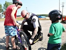 Turner Valley RCMP Const. Ken Moore fixes a chain on Jeffrey Wiens bike as his brother Kyler looks on. The two received a 'ticket' for a free Freezie for wearing
