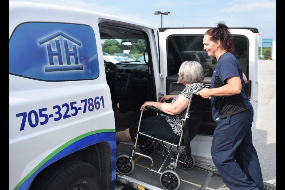 Rebecca Anderson, a PSW at Helping Hands, helps Barb Martin, the executive assistant to Helping Hands' board, into one of their vans. The agency is in desperate need of volunteers. Dave Dawson/OrilliaMatters