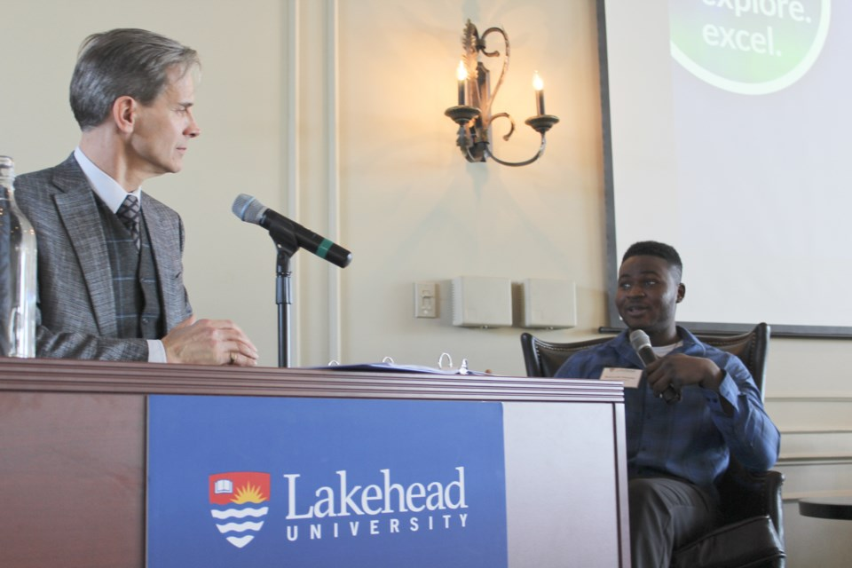 Dean Jobin-Bevans, left, principal of Lakehead University's Orillia campus, speaks with student Bolu Fabanwo on Wednesday during Lakehead's Report to Community at the Hawk Ridge Golf and Country Club. Nathan Taylor/OrilliaMatters