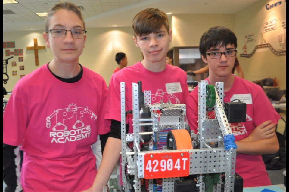Patrick Fogarty students Aiden Wilkins, Aidan Greatrix and Michael Whynot worked on perfecting their robot in the school's cafeteria Saturday before moving to the main competition stage in the school's gymnasium. Andrew Philips/Orillia Matters