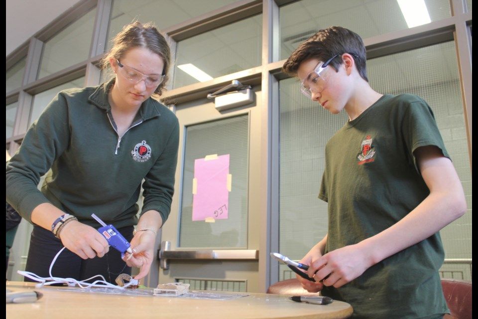 Olivia Klingspohn and Avery Warboys work on their Popsicle stick bridge Friday during the STEM industry tour's stop at Patrick Fogarty Catholic Secondary School. Nathan Taylor/OrilliaMatters