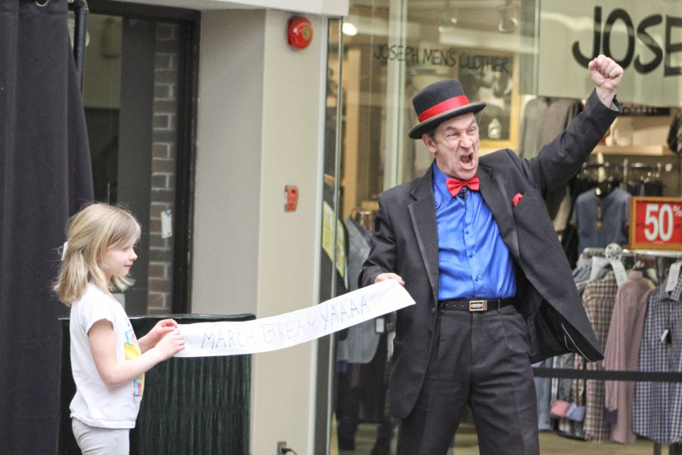 """An audience member helps magician Steve Baker unfurl a """"March break"""" banner during Baker's show Monday at the Orillia Square mall. Nathan Taylor/OrilliaMatters"""