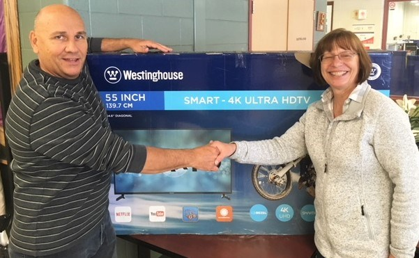 "Debbie Russell was the big winner at this weekend's 25th annual Simcoe Spring Home and Cottage Show. She won a 55"" Ultra HD TV courtesy of Wagner Lawn Care. She is shown with her prize alongside Glenn Wagner, manager of the show."